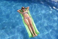 比基尼泳装和太阳镜说谎的年轻愉快的美丽的妇女在浮游物放松airbed在假期旅馆手段游泳池 库存照片