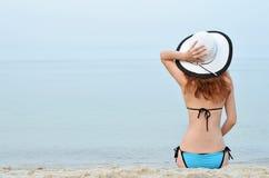 比基尼泳装和帽子的坐海滩,空间f性感的少妇 免版税库存照片