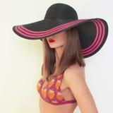 比基尼泳装和帽子的性感的女孩 免版税图库摄影