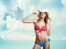 比基尼泳装和帽子的愉快的美丽的妇女在海滩 微笑 H 免版税库存照片