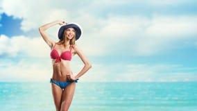 比基尼泳装和帽子的愉快的美丽的妇女在海滩 免版税库存图片