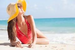 比基尼泳装和草帽的长发女孩在热带加勒比海滩 免版税库存图片
