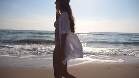 比基尼泳装和衬衣的愉快的妇女走在海滩的在海洋附近 帽子的年轻美丽的女孩享有生活的和 股票录像
