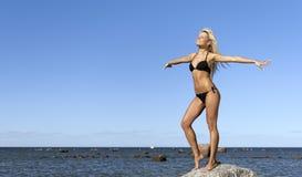 比基尼泳装女孩最近的摆在的岩石海&# 免版税库存照片