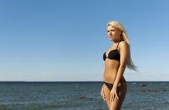比基尼泳装女孩最近的摆在的岩石海&# 库存图片