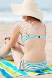 比基尼泳装妇女在和太阳被画的Sunhat支持在海滩 免版税库存照片