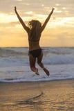 比基尼泳装妇女女孩跳跃的日落日出海滩 免版税库存照片