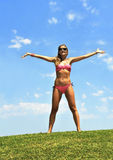 比基尼泳装开头的愉快的少妇武装对在夏天天空的空气 库存图片