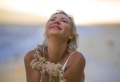 比基尼泳装摆在的美丽和性感的金发妇女愉快和轻松在假日使用以湿的逃走旅行的热带海滩 库存照片