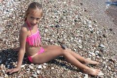 比基尼泳装摆在的美丽的小女孩 免版税库存照片
