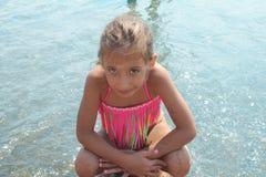 比基尼泳装摆在的美丽的小女孩 免版税图库摄影