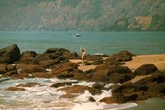 比基尼泳装有美好的身体的和太阳镜的女孩在海滩的红色石头附近 免版税库存照片