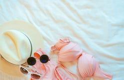 比基尼泳装泳装、太阳镜和草帽顶视图在床单 妇女的在手段床上的游泳衣和海滩辅助部件  图库摄影