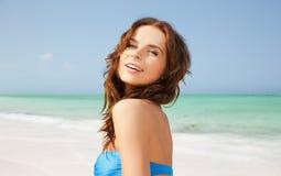 比基尼泳装泳装的愉快的妇女在热带海滩 图库摄影