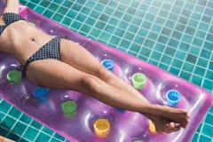 比基尼泳装游泳池的美丽的少妇在床垫inflat 免版税库存图片