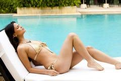 比基尼泳装游泳池边晒日光浴的妇女&# 免版税图库摄影