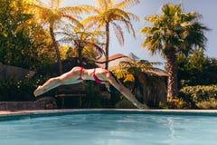 比基尼泳装潜水的妇女到游泳池里 图库摄影