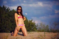 比基尼泳装的一个美丽的女孩倾吐沙子 库存照片