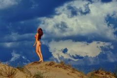 比基尼泳装的一个美丽的女孩倾吐沙子 库存图片