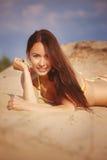 比基尼泳装的一个美丽的女孩倾吐沙子 免版税库存图片