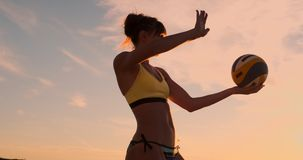 比基尼泳装的一美女有在日落的一个球的准备好做在海滩的服务跃迁在排球比赛 影视素材