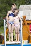 比基尼泳装的两个姐妹在游泳池附近 热夏天 图库摄影