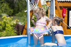 比基尼泳装的两个姐妹在游泳池附近 热夏天 免版税图库摄影