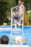 比基尼泳装的两个姐妹在游泳池附近 热夏天 库存照片