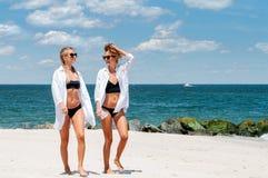 比基尼泳装的两个愉快的女孩在海滩 获得的最好的朋友乐趣,暑假假日生活方式 免版税库存图片