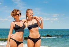 比基尼泳装的两个愉快的女孩在海滩 获得的最好的朋友乐趣,暑假假日生活方式 免版税库存照片