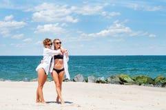 比基尼泳装的两个愉快的女孩在海滩 获得的最好的朋友乐趣,暑假假日生活方式 免版税图库摄影
