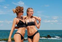 比基尼泳装的两名愉快的妇女在海滩 获得的最好的朋友乐趣,暑假假日生活方式 库存照片