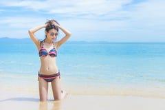 比基尼泳装的亚裔女孩在海滩 免版税图库摄影