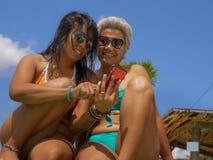 比基尼泳装的亚裔女朋友一起享受夏天休假的在热带海滩胜地游泳场获得乐趣使用手机 图库摄影