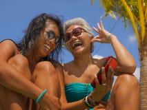 比基尼泳装的亚裔女朋友一起享受夏天休假的在热带海滩胜地游泳场获得乐趣使用手机 库存图片