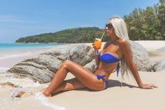 比基尼泳装的亭亭玉立的白肤金发的长发妇女在热带海滩 图库摄影