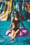 比基尼泳装的俏丽的深色的妇女在可膨胀的圆环 库存照片