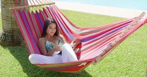 比基尼泳装的单身妇女读在吊床的一本书 股票录像