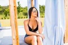 比基尼泳装的可爱的少妇在游泳池旁边的一个休息室沙发 新的成人 免版税库存图片