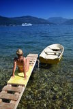 比基尼泳装的可爱的年轻金发碧眼的女人观看当游轮的通过  免版税图库摄影
