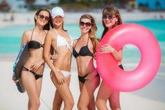 比基尼泳装的四名妇女有在海洋附近的保险索的 库存图片