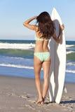 比基尼泳装的女子冲浪者与在海滩的冲浪板 库存图片