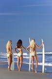 比基尼泳装的女子冲浪者与在海滩的冲浪板 免版税库存照片