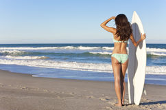 比基尼泳装的女子冲浪者与在海滩的冲浪板 库存照片
