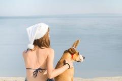 比基尼泳装的女孩和狗在圣诞节的海边假期 库存照片