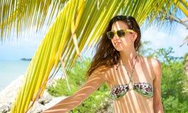 比基尼泳装的女孩在一个热带海滩 免版税库存图片