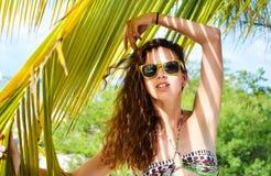 比基尼泳装的女孩在一个热带海滩 免版税库存照片