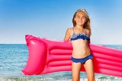比基尼泳装的女孩有桃红色可膨胀的床垫的 免版税图库摄影