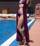 比基尼泳装的女孩由海滩胜地游泳池 免版税库存图片