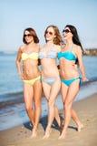 比基尼泳装的女孩走在海滩的 库存图片